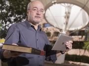 Jim Goulka holds an old encyclopedia in one hand and an iPad in the other to illustrate his diverse career path.