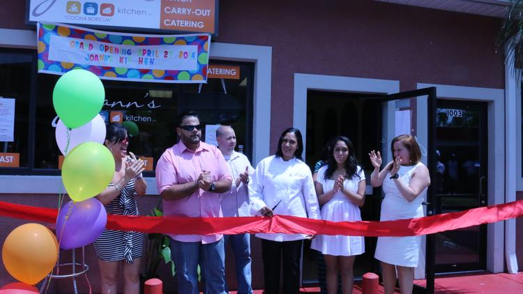 Restaurant owner Joann Corvoisier and her family readies the ribbon to be cut...