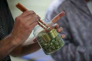 An employee pulls marijuana out of a large canister for a customer at the LoDo Wellness Center in downtown Denver, Colorado.