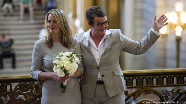 Sandy Stier, left, and Kris Perry wave after being married at City Hall in San Francisco on June 28, 2013.