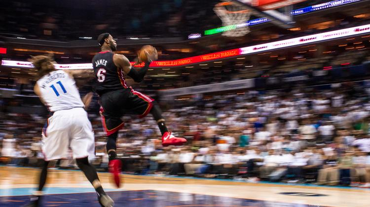 In this slow-shutter exposure photo, Heat forward LeBron James soars toward the basket. The Miami Heat defeated the Charlotte Bobcats 109-98 in an April 28, 2014, game at Time Warner Cable Arena in Charlotte. The victory sealed Miami's four-game sweep in round one of the 2014 NBA playoffs.