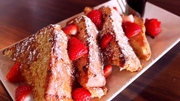 Max's Wine Dive brunch menu includes creme brûlée french toast topped with strawberries and powdered sugar.