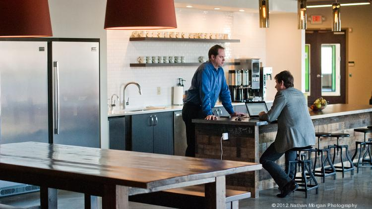 Jason McMahan, left, talks with John Mensel, while working at Concept Technology in the new cafe, part of the reinnovation at the new germantown office.