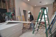 Johnny Corrales, left, and Carlos Carson of Corrales Contracting Corp. prep sheetrock for an apartment at 83 Beaver St. in downtown Albany.