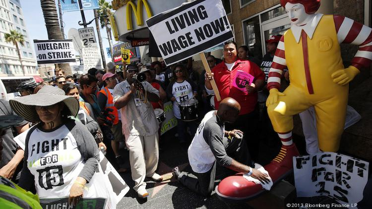 Fast food workers and supporters protested for a $15 per hour wage outside of the McDonald's restaurant at Hollywood and Highland in Los Angeles, California in August 2013.