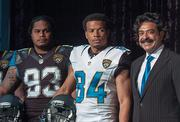 Jaguars players Tyson Alualu, Cecil Shorts III stand with owner Shahid Khan during a press conference introducing the team's new uniforms.