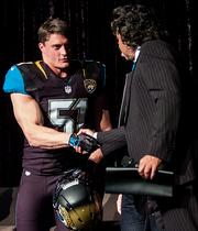 Posluszny shakes hands with team owner Shahid Khan during the Jaguars team press conference introducing the team's new uniforms.