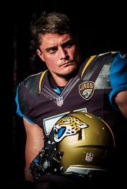 Jaguars linebacker Paul Posluszny listens to team owner Shahid Khan during the Jaguars team press conference introducing the team's new uniforms.