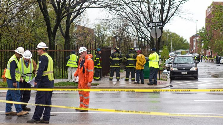 Emergency crews congregate along 26th Street between Charles and St. Paul streets following the street collapse.