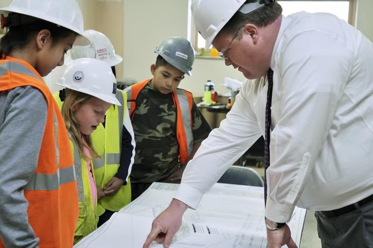 Jared Minter, director, education studio, Lantz-Boggio Architects, shows 5th graders at Brown International Academy in Denver the construction in their school. The school is renovating and adding space.