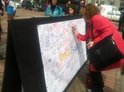 People stopped to sign banners posted by the One Boston fund at the Copley Square memorial honoring Marathon attack victims.