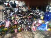 In one of the Copley Square memorials, people hung running shoes on a police barricade.