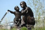 """Mothers and Children Anxiously Awaited Return of Their Loved Ones"" is a sculpture by Carolyn Manto. It has been installed at Smale Park."