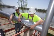 Jeff Brewsaugh, left, and Kerek  Clifton torque the Allen bolts on the stainless steel swing Superior Steel Service is building at Smale Park.