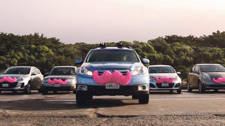Lyft cars are personal vehicles driven by local drivers. The cars are identifiable by the pink mustaches attached to their grills.