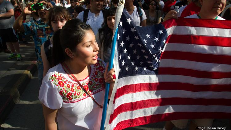 """Gardenia Vivas-Jimenez, of Seattle, marches at a May 1 rally in Seattle for immigrant rights.  """"The flag represents a better life for us,"""" she said. Immigration reform has now drawn the support of Tea Party leaders."""