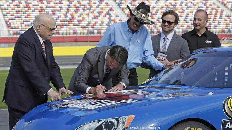 Richard Petty (in hat), Marcos Ambrose (far right), Bruton Smith (far left), Marcus Smith and Gov. Pat McCrory (signing proclamation) at the speedway earlier this month.