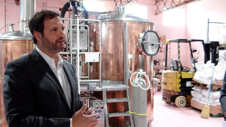 Developer and restauranteur Marty Kotis talks to visitors to his Pig Pounder Brewery, which began brewing beer this week that will be served at his area restaurants.