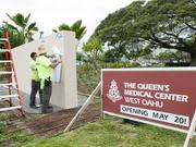 Workers measure and sketch out the specifics of the signage that will go out front at The Queen's Medical Center West Oahu.
