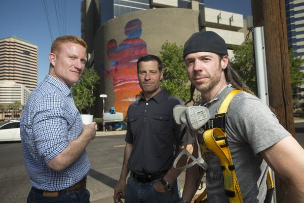 """(Left-right) Tim O'Neil, Robert """"Bob"""" Karber and James Bullough. O'Neil and Karber manage and own the building in the background at 2828 N. Central Ave. in Phoenix. Bullough helped paint the six-story mural."""