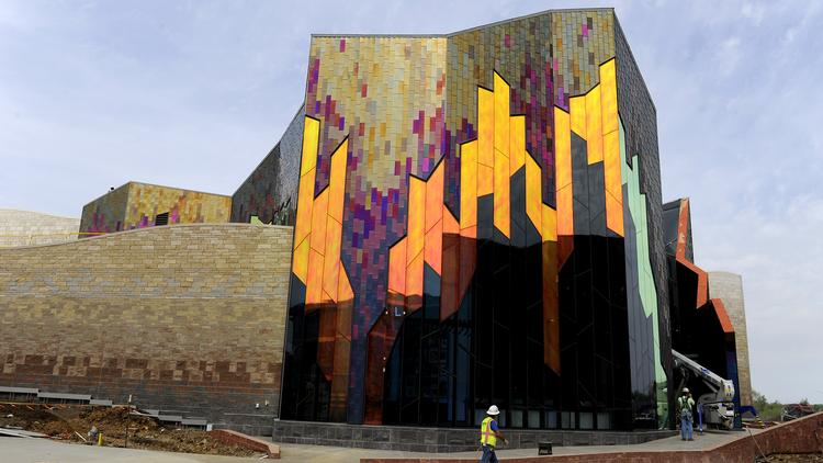 A construction worker walks by the nearly-opened Museum at Prairiefire in Overland Park. The exterior of the building features dichroic glass and Kansas limestone that contains fossils. The exterior is designed to convey the flames of Prairiefire and a rebirth. The museum is slated to open May 12.