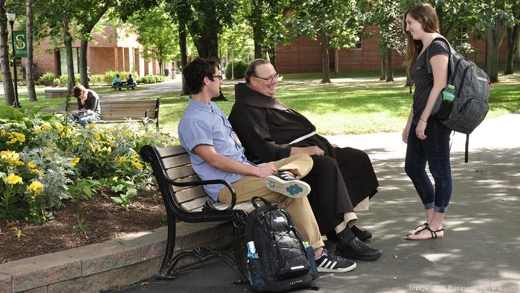 Siena College president Father Kevin Mullen, pictured here talking to students, will leave the school in August to lead the largest Franciscan community in the U.S.