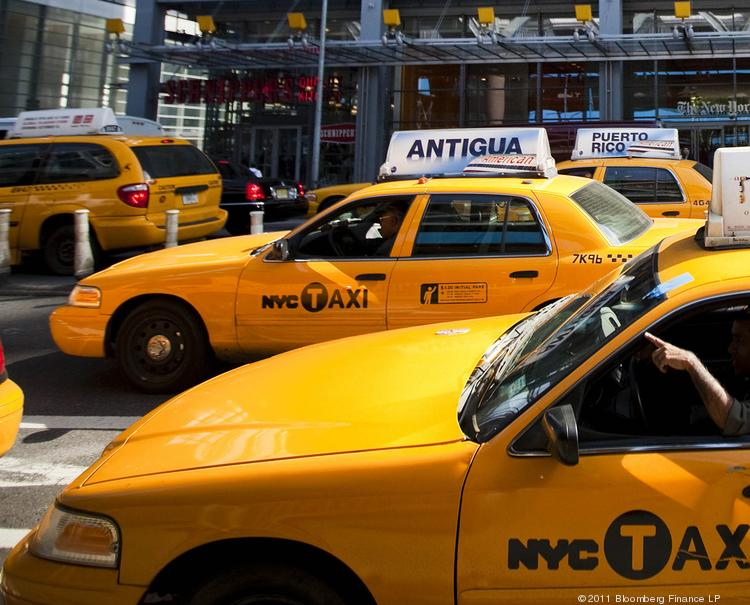 Taxi cabs swarm down a New York street.