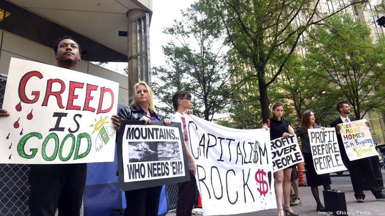 "Half a dozen protesters had gathered outside Bank of America's (NYSE:BAC) annual shareholder meeting by about 11 a.m. on Wednesday, May 7. They identified themselves as being from Charlotte Environmental Action and carried ""sarcastic"" messages."