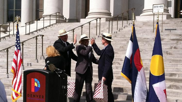 Governor John Hickenlooper and Mayor Michael Hancock high-five after the announcement of nonstop service between DIA and Panama City at a press conference Wednesday, May 7.
