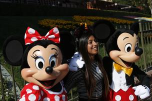 Walt Disney Co. characters Minnie Mouse and Mickey Mouse take pictures with a guest at Disneyland Park, part of the Disneyland Resort, in Anaheim, California, U.S., on Friday, May 24, 2013.