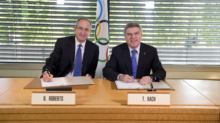 Comcast Chairman and CEO Brian Roberts signs a deal with International Olympic Committee Chairman Thomas Bach to maintain broadcast rights for the Olympics through 2032.