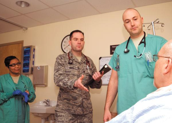 Military Care: The Wright-Patterson Medical Center is undergoing $90 million in renovations.  (L-R) SSgt. Ashleigh Lankford, medical technician; Major (Dr.) Bryan White, chief of cardiology; and 2Lt. Dennis Watson, staff nurse, talk to Daniel Druzbacky, a patient at the hospital.