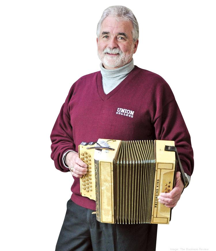 Michael Newell, CEO of Ener G Rotors with his grandfather's button accordion. Newell's bands may have broken up, but he still plays and has a collection of five accordions.