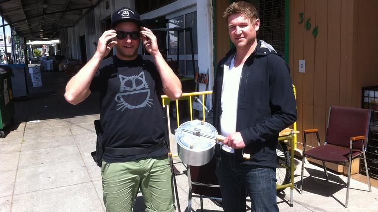 Matthew McKee (left) and Brad Butler with the Whirley Pop popper. They also roasted beans early on in a wok with a wooden spoon to stir.