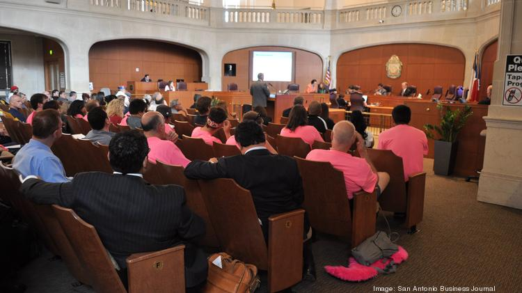 Lyft and Uber drivers and supporters listen to a presentation in front of the San Antonio City Council.