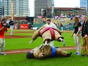 A pair of 'lucky' baseball fans take part in the between-inning tradition of Sumo wrestling during a Greensboro Grasshoppers home game.