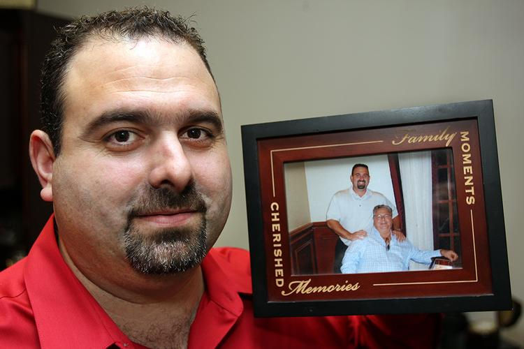 Apex Office Products Inc.'s Alex Llorente with a photo in his office of he and his father, Aurelio Llorente Jr.