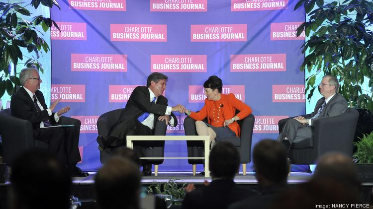 Piedmont CEO Tom Skains (second from left) greets Duke CEO Lynn Good during the CEO Panel at the Charlotte Business Journal's Energy Inc. conference.