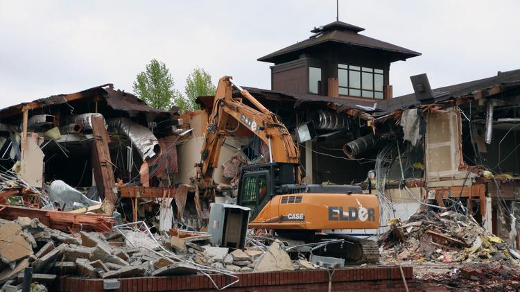 Crews from Elder Demolition of Portland will spend about four weeks tearing down the former Ports O'Call building and another four weeks excavating the foundation to set the stage for construction of the new $150 million headquarters of Daimler Trucks North America on Swan Island.