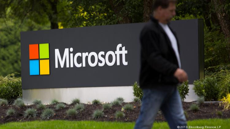A pedestrian walks past signage displayed at the Microsoft Corp. campus in Redmond.