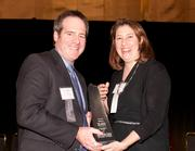 Dr. John Hawkins, chief of psychiatry at Lindner Center of Hope, accepts the winner's award in the Innovator category from Valerie Bogdan-Powers, vice president of group operations at Horan.