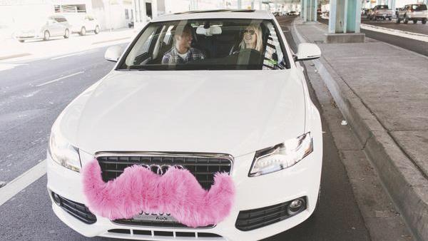 Lyft drivers attach pink mustaches to their front grilles.