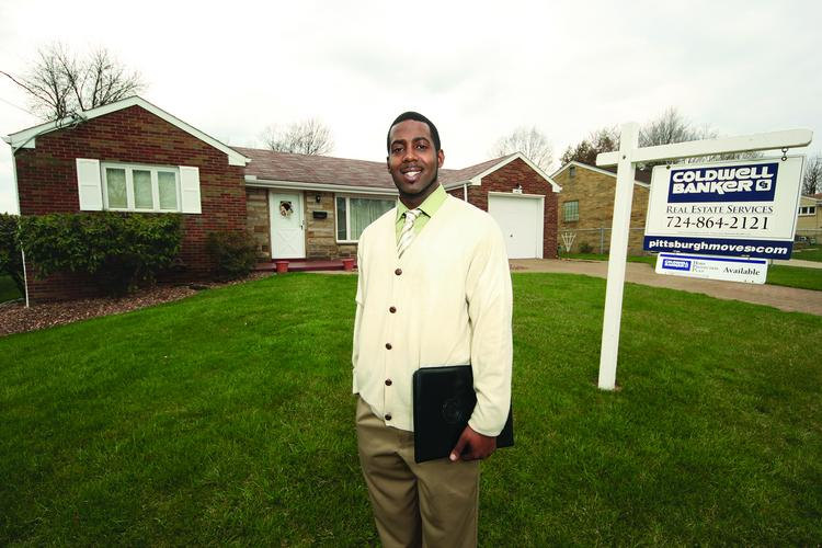 Coldwell Banker Sales Agent Barrington Bogle Jr. stands in the front yard of a three-bedroom, two-bath house on Lynne Drive in North Huntingdon that is listed at $139,900.