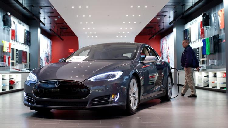 Tesla Motors' Model S connected to a charger sits on display at a company store.