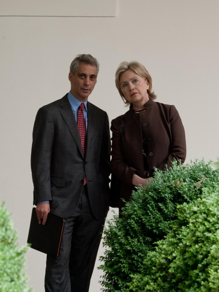 Then-White House Chief of Staff Rahm Emanuel and then-Secretary of State Hillary Clinton watch President Barack Obama speak at a 2009 press conference.