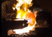 A steel tube is heated to shape a dome at each end for CP Industries' gas cylinder line.