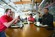 Googlers, from left, Tony Trainor, Victoria Jones and John Mbuga are busy on their smartphones even while eating.