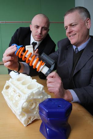 3DLT's Pablo Arellano, left, and John Hauer with printed objects, including this functioning spring.