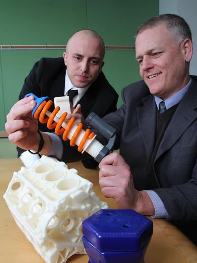 3DLT's Pablo Arellano, left, and John Hauer with printed objects, including this functioning spring. 3DLT was part of UpTech's second class of startups.