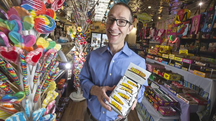 Michael Sasso, founder and president of Sasso Candy Company, poses with his first product — coffee caramel and dark chocolate candy bars currently stocked by retailers like Powell's Sweet Shoppe in Los Gatos.